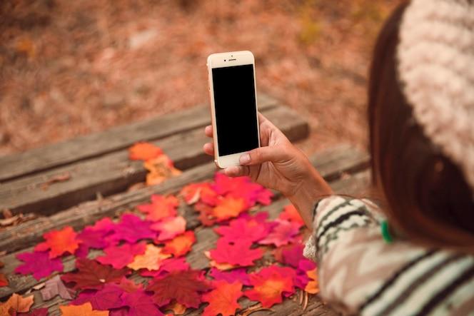 Mujer irreconocible con teléfono inteligente en el parque