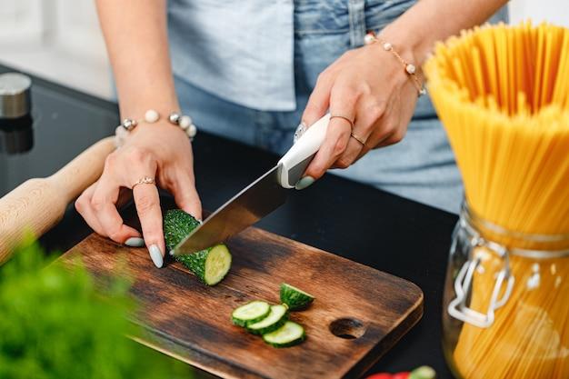 Mujer irreconocible cortando pepino sobre tabla de madera de cerca