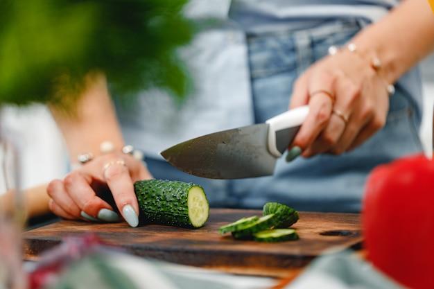 Mujer irreconocible cortando pepino sobre tabla de madera cerrar