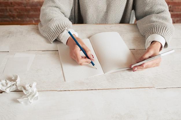 Mujer irreconocible escribiendo en el cuaderno