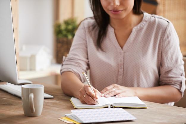 Mujer irreconocible escribiendo en planificador