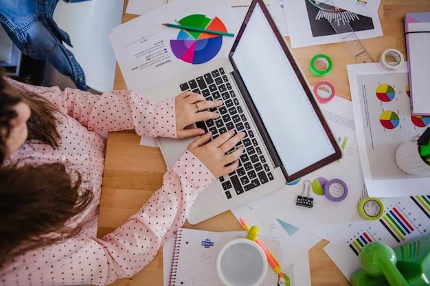 Mujer irreconocible que mecanografía el ordenador portátil en oficina