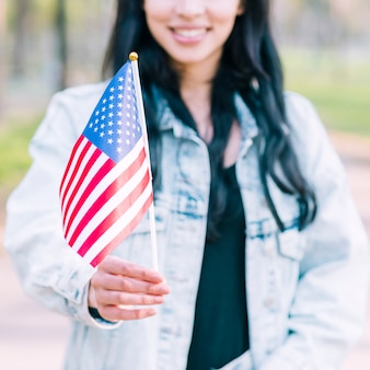 Mujer irreconocible que sostiene la bandera estadounidense durante la celebración del cuatro de julio