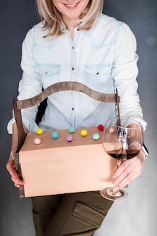 Mujer irreconocible que sostiene los regalos en cesta de madera y el vidrio de vino rojo en fondo oscuro. caja de regalo, presente, concepto de celebración.