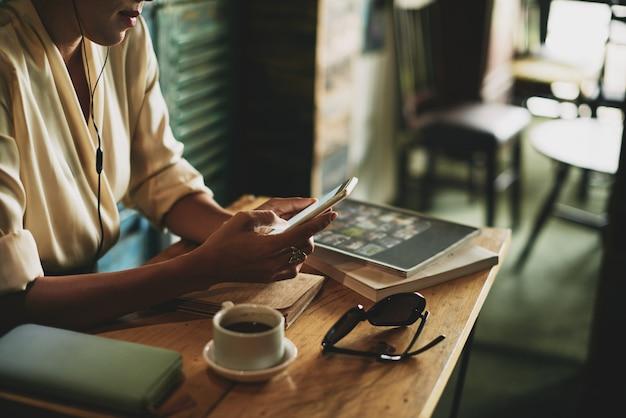 Mujer irreconocible sentada en la cafetería y escuchando música en el teléfono inteligente
