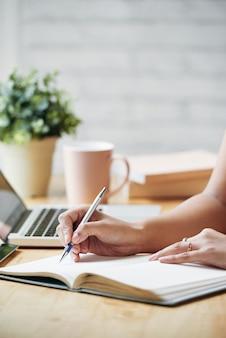 Mujer irreconocible sentada en el escritorio en el interior y escribiendo en planificador