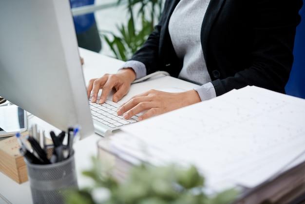 Mujer irreconocible sentada en el escritorio en la oficina y escribiendo en el teclado