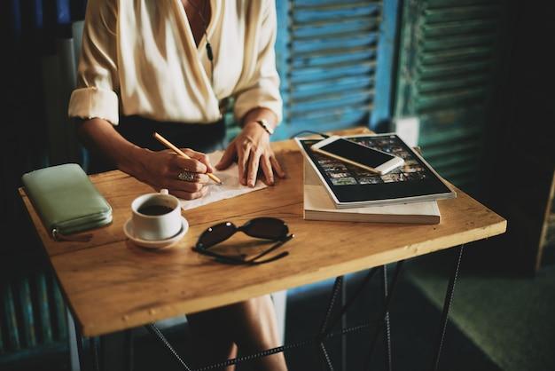 Mujer irreconocible sentada a la mesa en el café y escribiendo en una servilleta