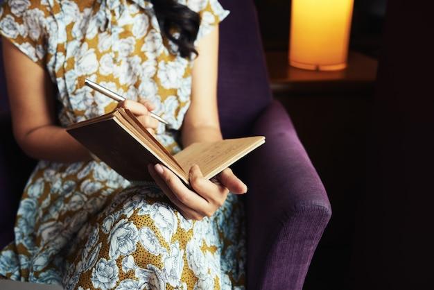 Mujer irreconocible sentada en un sillón y escribiendo en el diario
