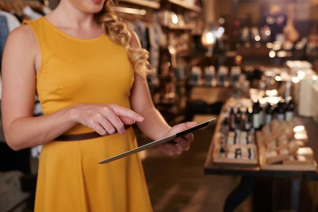 Mujer irreconocible con tableta en grandes almacenes