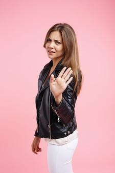 Mujer irritada y cansada muestra señal de stop con la mano