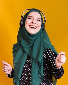 Mujer islámica alegre disfrutando de la música sobre fondo amarillo
