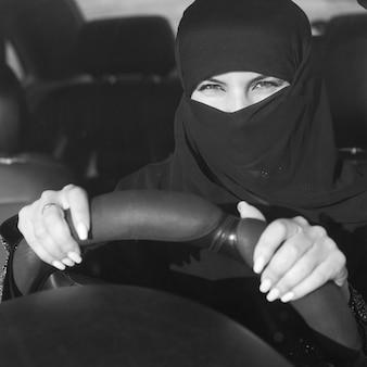 Mujer islámica conduciendo un coche. imagen en blanco y negro.