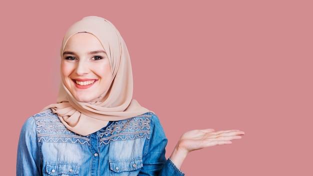 Mujer islámica feliz presentando algo en el fondo