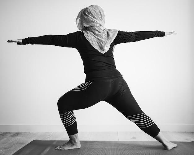 Mujer islámica haciendo yoga en la habitación.