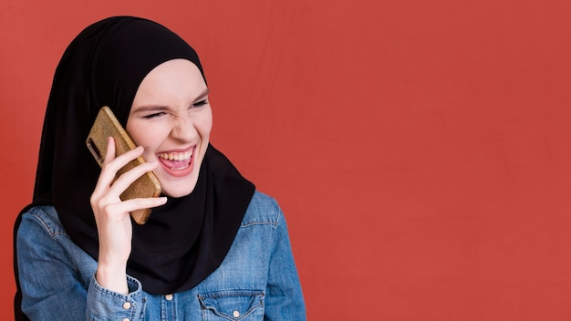 Mujer islámica en hijab llamando por teléfono