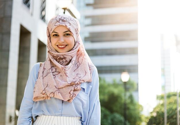 Mujer islámica de pie y sonriendo en la ciudad.