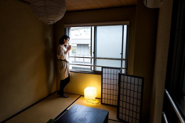 Mujer japonesa bebe té y mira por la ventana