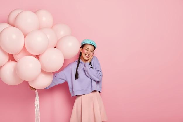 La mujer japonesa bonita llena de alegría mantiene los ojos cerrados, se complace en recibir felicitaciones por ingresar exitosamente a la universidad, sostiene globos