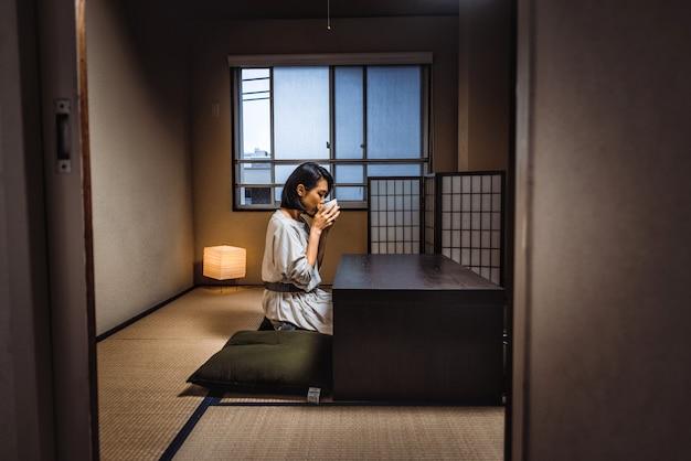 Mujer japonesa se sienta en casa y bebe té