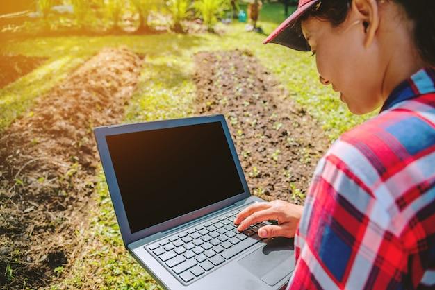 Mujer en el jardín con el portátil.
