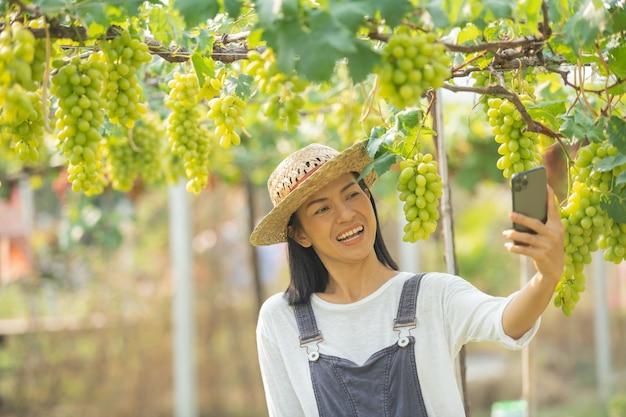 Mujer en el jardín mediante teléfono móvil para recibir pedidos de su uva.