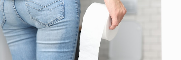 Mujer en jeans azul está de espaldas y sostiene un rollo de papel higiénico en la mano frente al primer plano del inodoro. concepto de urología de micción frecuente.