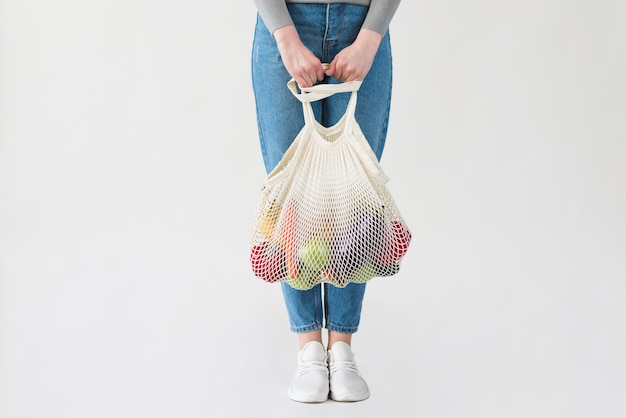 Mujer en jeans con bolsa reutilizable con comestibles