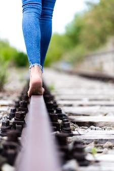 Mujer en jeans caminando descalzo por los rieles del tren