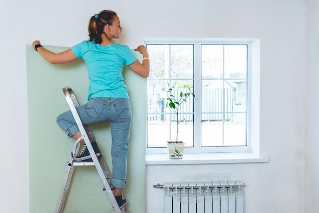 Mujer en jeans y camiseta turquesa de pie en la escalera y sosteniendo un pedazo de papel tapiz