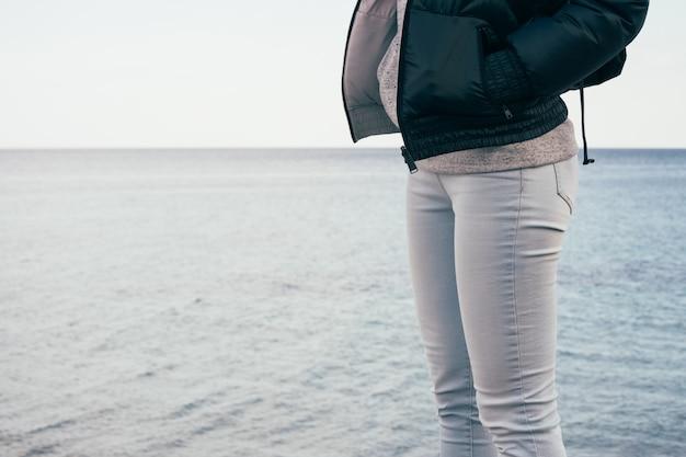 Mujer en jeans y chaqueta de pie en el fondo del mar