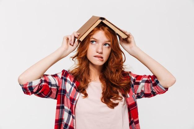 Mujer de jengibre en camisa con libro en la cabeza como techo