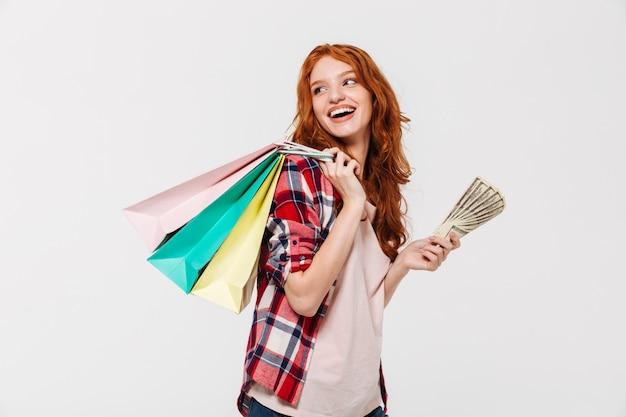 Mujer de jengibre complacida en camisa sosteniendo paquetes en el hombro con dinero en mano mientras mira hacia atrás