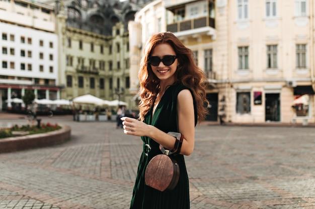 Mujer de jengibre en elegantes gafas de sol sonriendo afuera