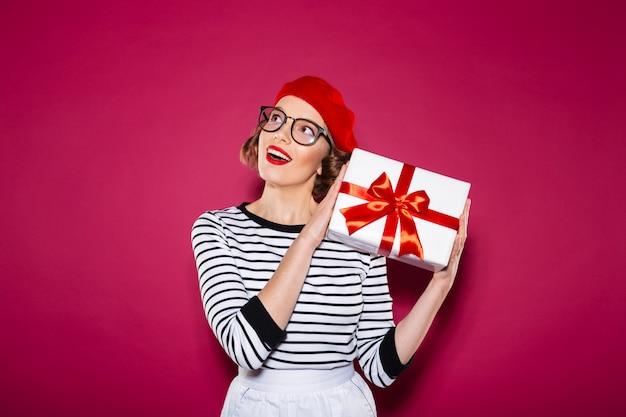 Mujer de jengibre feliz intrigada en anteojos con caja de regalo cerca de la oreja y mirando hacia arriba sobre rosa
