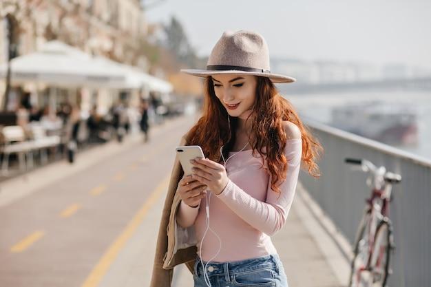Mujer de jengibre interesada con teléfono en manos comprobando el correo en la muralla de la ciudad