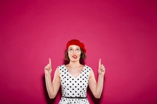 Mujer de jengibre intrigada en vestido apuntando y mirando hacia arriba mientras muerde su labio sobre rosa