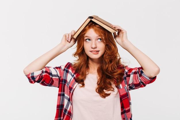 Mujer de jengibre pensativa en camisa con libro sobre su cabeza