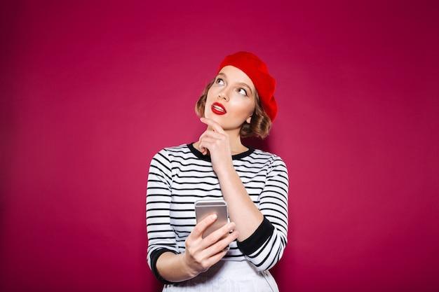 Mujer de jengibre pensativa con smartphone y mirando hacia arriba sobre rosa