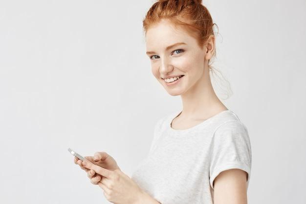 Mujer de jengibre sonriendo sosteniendo teléfono twitteando o usando las redes sociales en la pared blanca