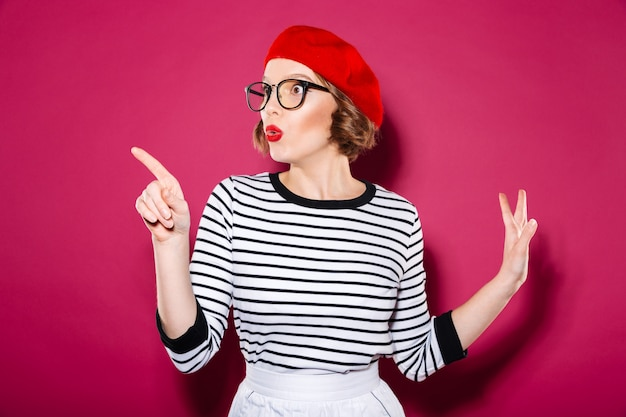 Mujer de jengibre sorprendida en anteojos apuntando y mirando a otro lado sobre rosa