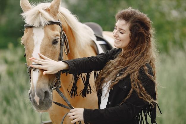Mujer jinete hablando con su caballo en un rancho. la mujer tiene mucho tiempo y ropa negra. ecuestre femenina tocando su caballo marrón.