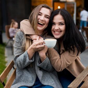 Mujer joven abrazada por su amiga