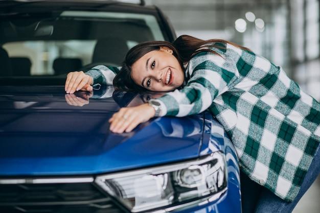 Mujer joven abrazando un automóvil en una sala de exposición de automóviles
