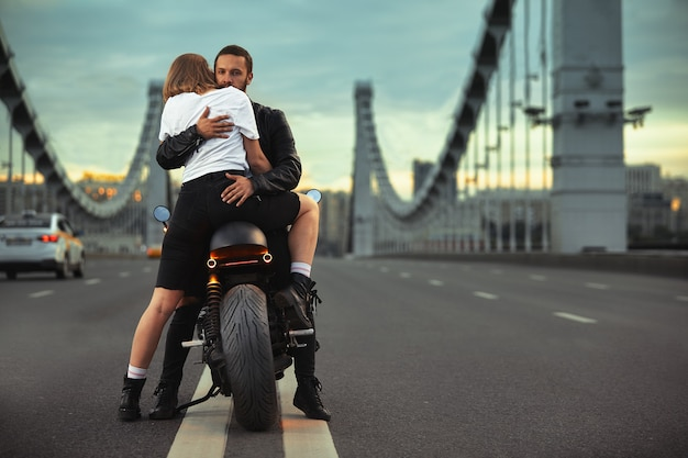 Mujer joven abrazando a hombre lindo con elegante chaqueta de cuero negro sentado en una motocicleta deportiva en el puente de la ciudad al atardecer y besos