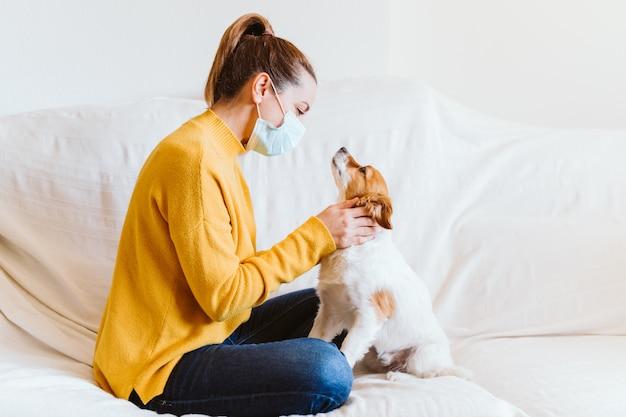 Mujer joven abrazando a su lindo perro pequeño en casa, sentado en el sofá, con máscara protectora. concepto de quedarse en casa durante el coronavirus covid-2019
