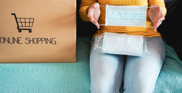 Mujer joven abriendo la caja de papel con máscaras protectoras faciales