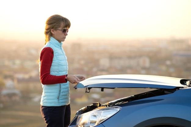 Mujer joven abriendo el capó del coche averiado que tiene problemas con su vehículo