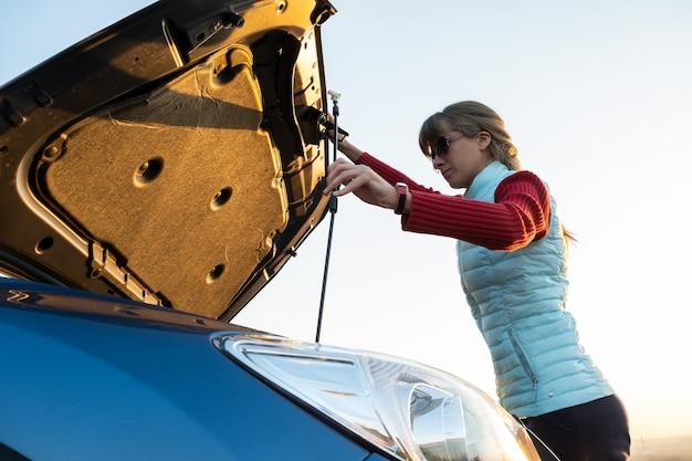 Mujer joven abriendo el capó del coche averiado que tiene problemas con su vehículo.