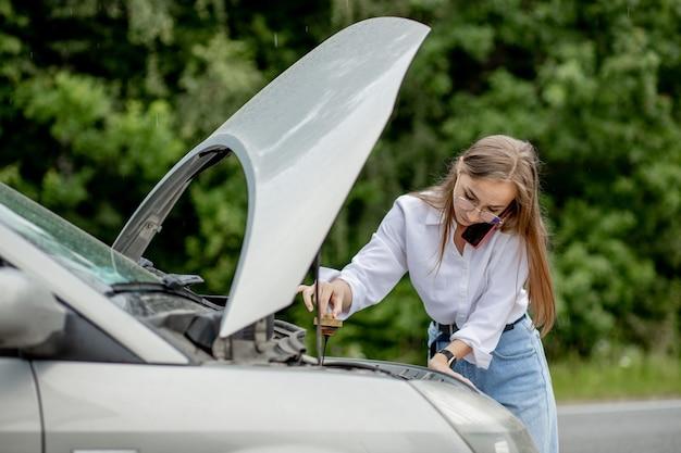 Mujer joven abriendo el capó del coche averiado tiene problemas con su vehículo